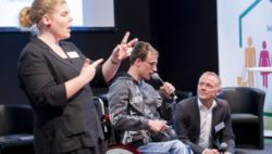 Photo: A speaker in a wheelchair speaking in the REHACARE forum. A sign language interpreter translates what is said for the audience; Copyright: Messe Düsseldorf