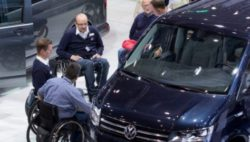 Photo: Hall 6, at a stand for car customization, several trade fair visitors in wheelchairs talking to exhibitors